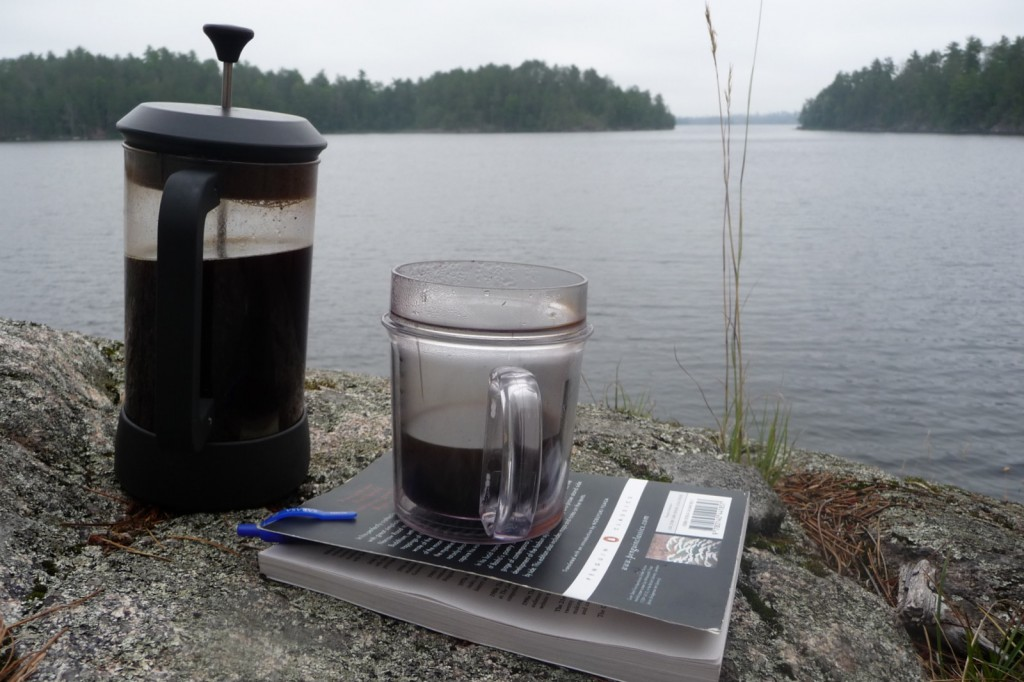A pot of coffee, a book and a lake